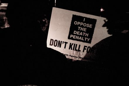 Image of an anti-death penalty campaign march with a banner stating 'I oppose the death penalty'. Photo is by Scott Langley